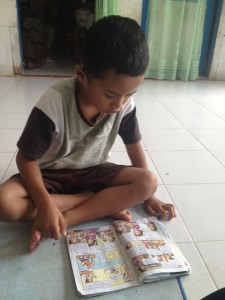 The son of our new Lake Toba friend reading from his school book. He was really good, but I couldn't understand a word of what he was reading.